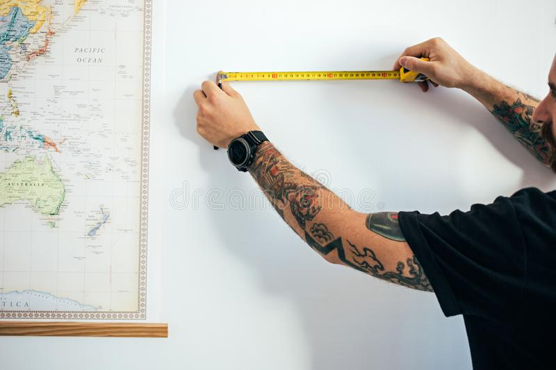 close-up-view-male-arms-tattoos-watch-uses-measuring-tape-to-establish-construction-work-measurments-prepares-new-house-101042281